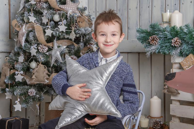 有银色星的男孩坐爬犁在圣诞树下 免版税库存图片