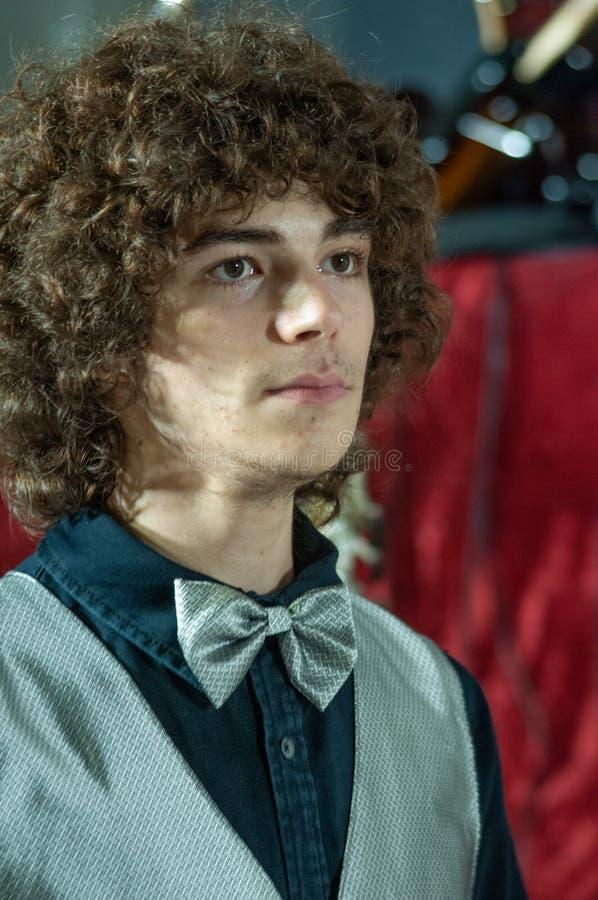 有银色蝶形领结的,银色背心年轻典雅的男孩,微笑,在一个音乐音乐会前 免版税库存图片