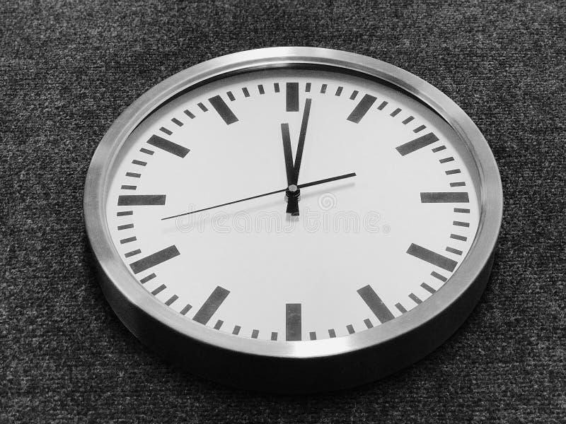 有银色边缘的白色壁钟在灰色背景 免版税图库摄影