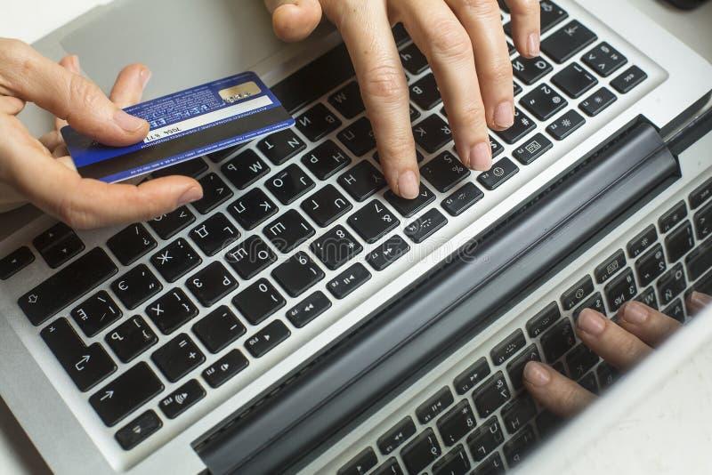 有银行卡签证的女性手在计算机的MacBook赞成键盘 在互联网上的社论说明购物 免版税库存图片