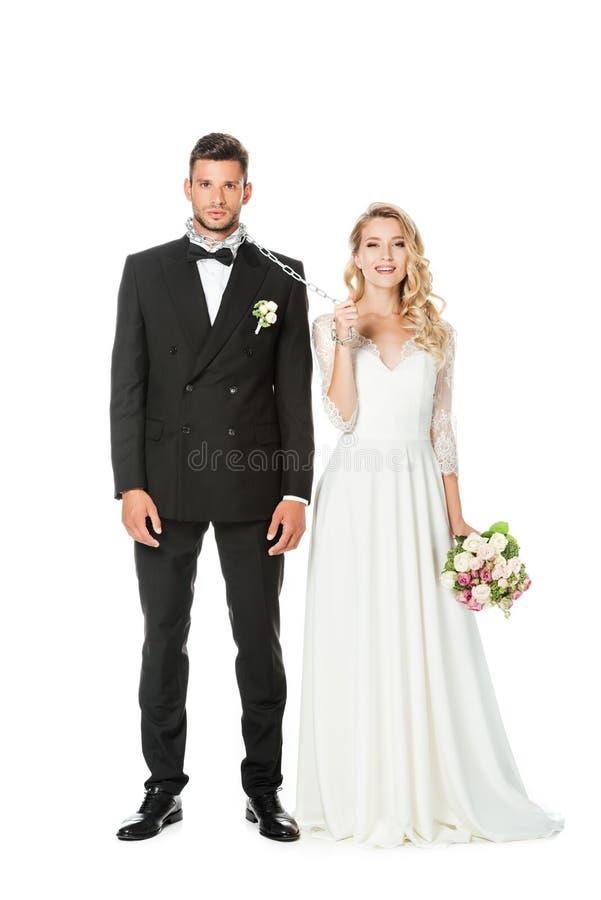 有链子的美丽的年轻新娘和看照相机的leashed新郎 免版税库存图片