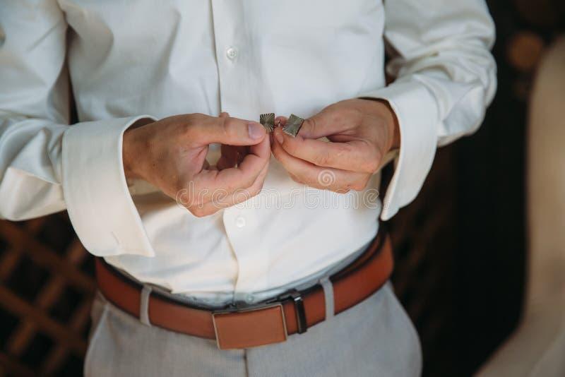 有链扣的新郎手 典雅的绅士clother、白色衬衣和棕色传送带 库存图片