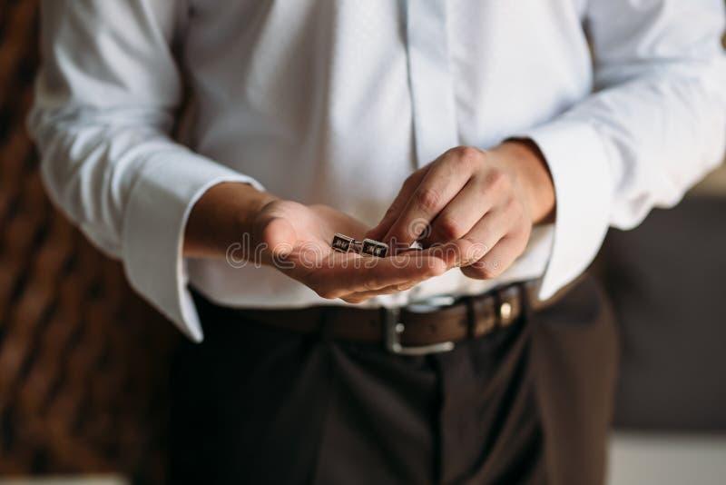 有链扣的新郎手 典雅的绅士clother、白色衬衣和棕色传送带 免版税库存图片