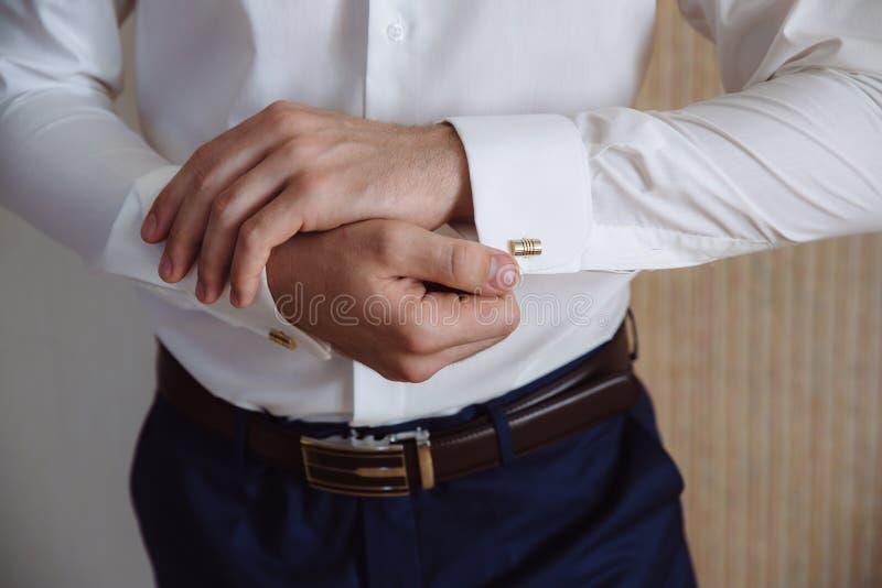有链扣的新郎手 典雅的绅士clother,白色衬衣 免版税图库摄影