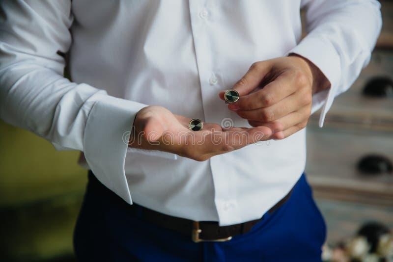 有链扣的新郎手 典雅的绅士clother,白色衬衣 免版税库存图片