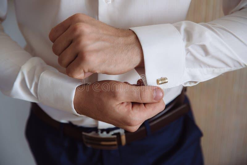 有链扣的新郎手 典雅的绅士clother,白色衬衣 库存照片
