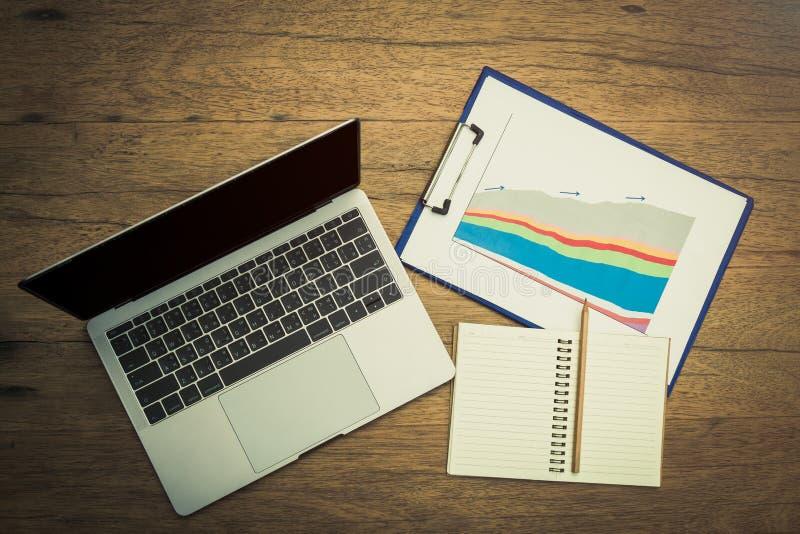 有销售图的采取的备忘录膝上型计算机和文具在检查数据以后 库存照片