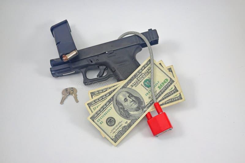 有锁、弹药和现金的手枪 免版税库存图片