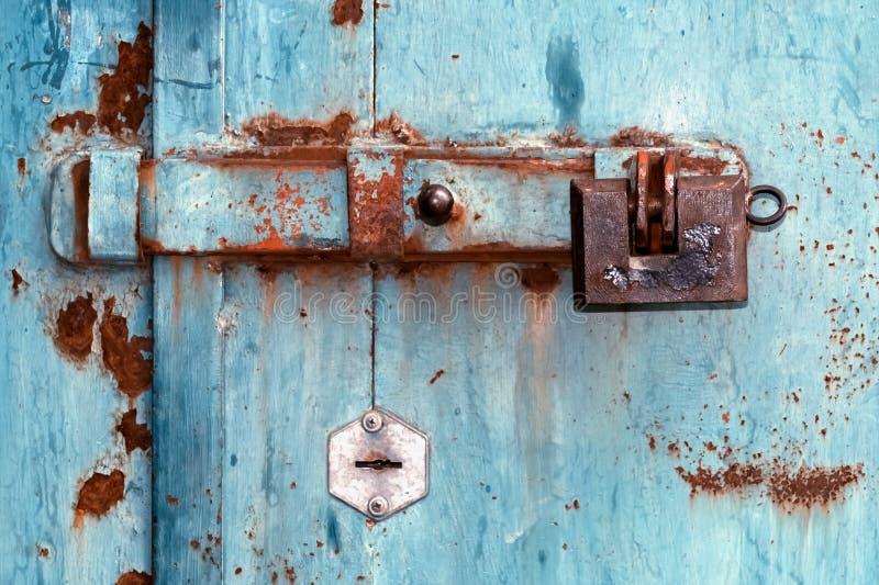有锁的老deadbolt在铁门 库存照片