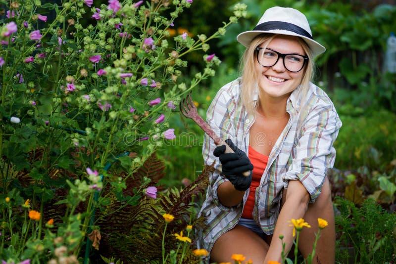 有锄的年轻微笑的花匠在她的手下朵花 免版税库存照片
