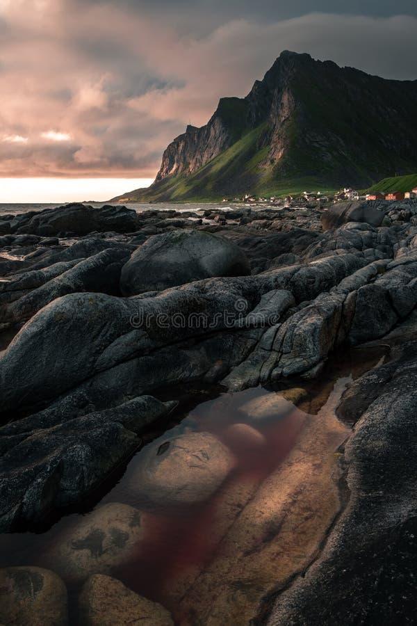 有锋利的山的村庄在日落在罗弗敦群岛 图库摄影