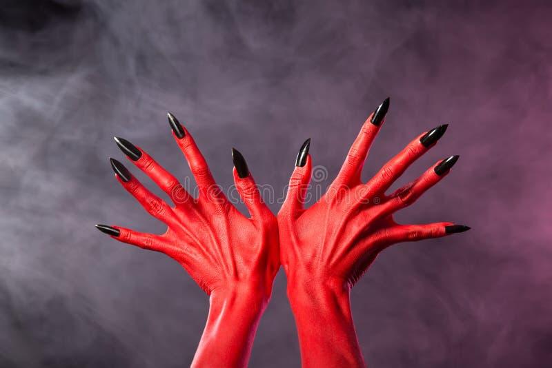有锋利的黑钉子的红魔手,极端身体艺术 库存照片
