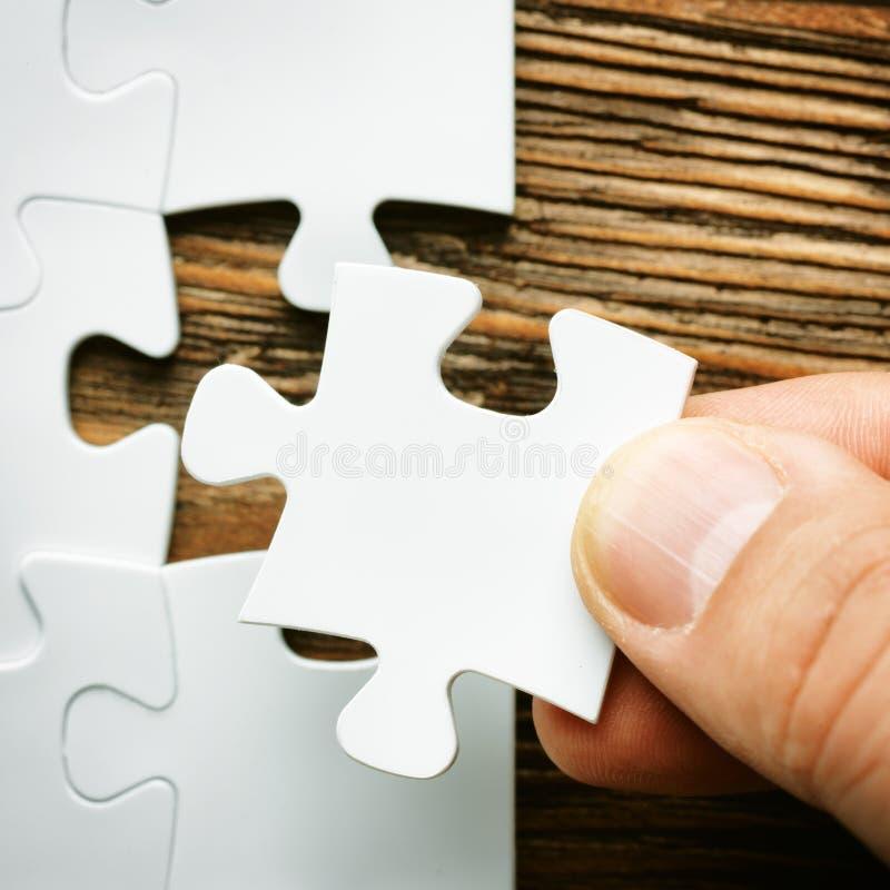 有错过的七巧板片断手 企业完成的最后的难题片断概念图象 库存图片