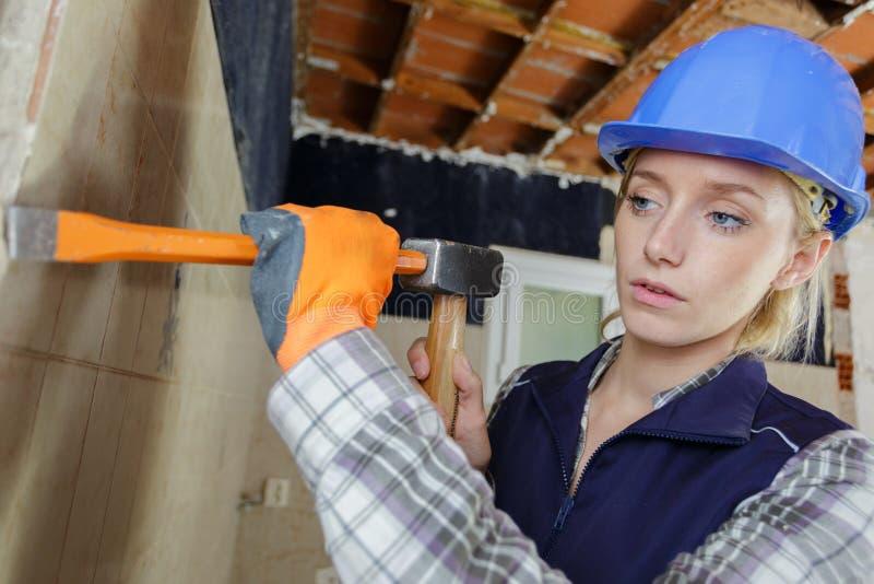 有锤子和凿子工作的妇女在客户房子里 图库摄影