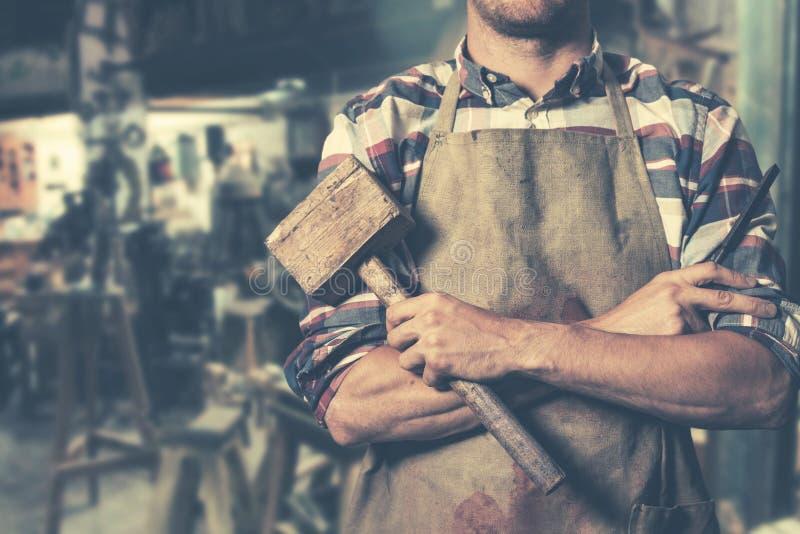 有锤子和凿子的木匠在手上在车间 库存照片