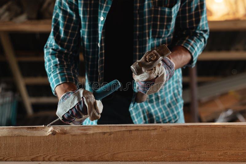有锤子和凿子的木匠处理木头 木匠在工作在车间 库存照片