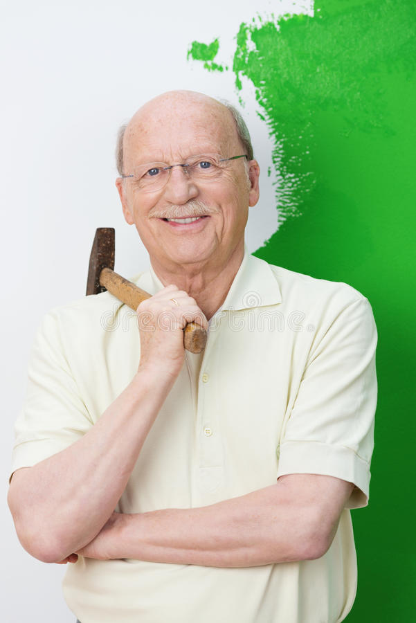 有锤子的微笑的确信的老人 库存照片