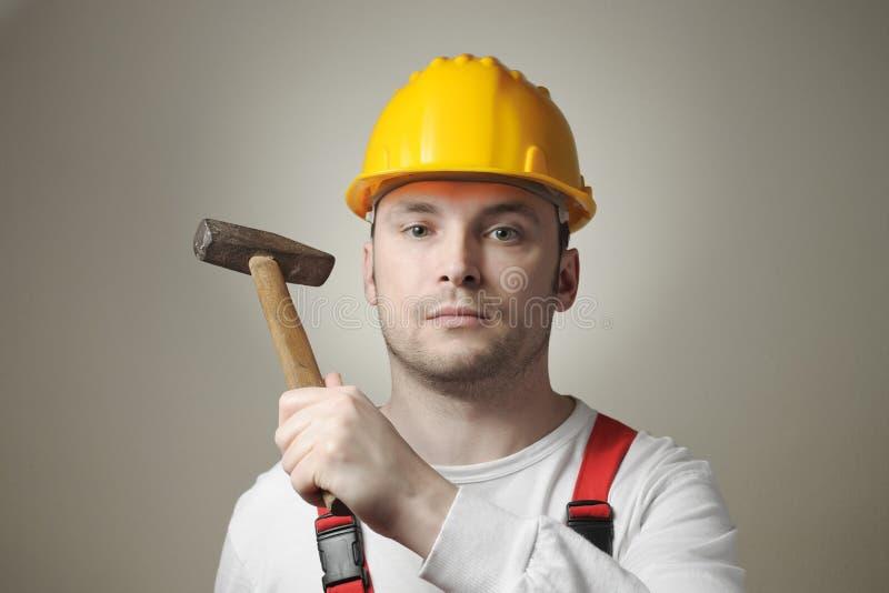 有锤子的年轻工人 库存图片
