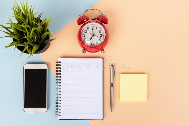 有键盘的,咖啡办公桌,智能手机,闹钟,稠粘的笔记,罐植物 免版税图库摄影