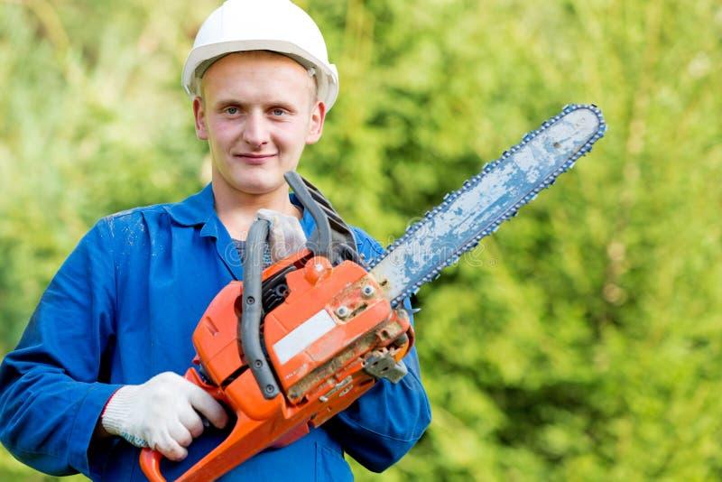 有锯的伐木工人工作者在森林背景的工作穿戴 免版税库存图片