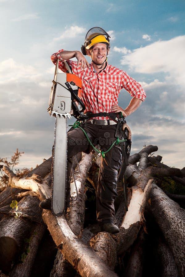 有锯的微笑的伐木工人 免版税库存照片