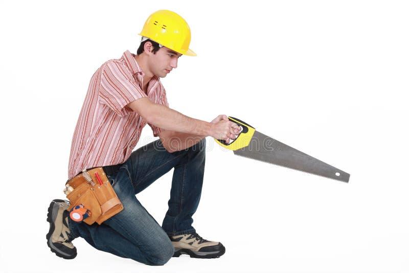 有锯的木匠 免版税图库摄影