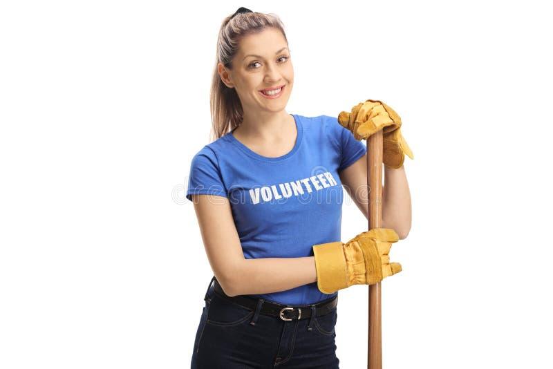 有锹和手套的年轻女性志愿者微笑对照相机的 免版税库存图片