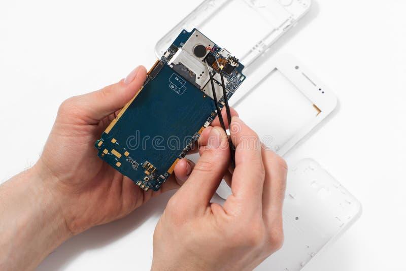 有镊子的安装工拆卸的智能手机 免版税库存图片