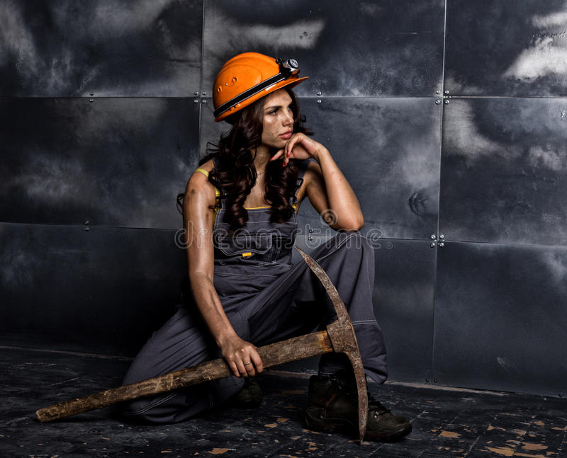 有镐的性感的女性矿工工作者,在他的赤裸身体的工作服,坐在钢墙壁背景的地板  免版税图库摄影