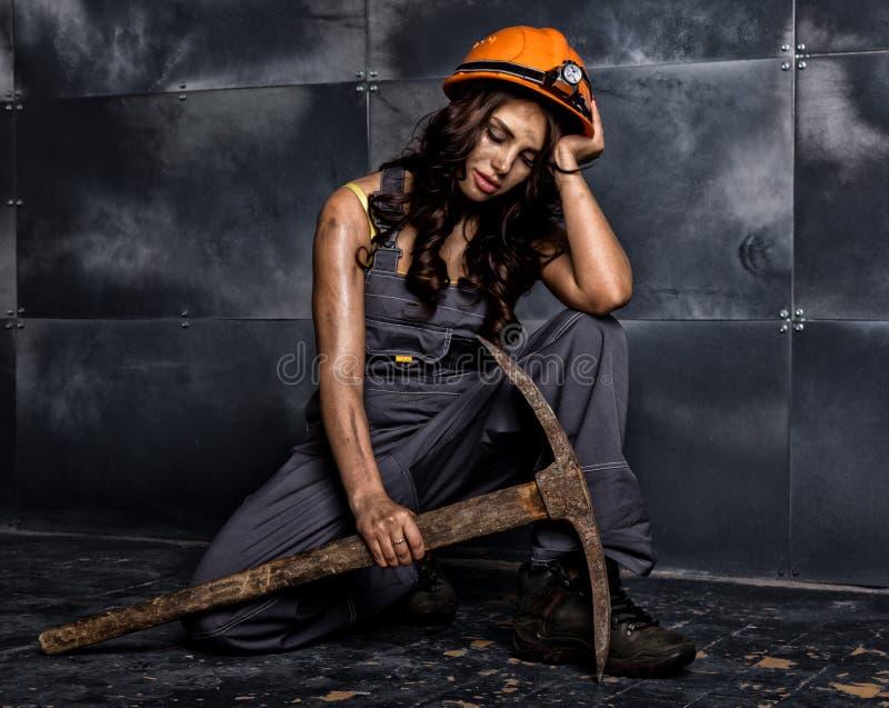 有镐的性感的女性矿工工作者,在他的赤裸身体的工作服,坐在钢墙壁背景的地板  免版税库存照片