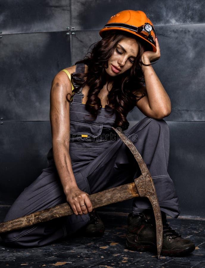 有镐的性感的女性矿工工作者,在他的赤裸身体的工作服,坐在钢墙壁背景的地板  免版税库存图片