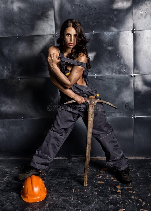 有镐的性感的女性矿工工作者,在他的赤裸身体的工作服 色情产业概念 免版税库存照片