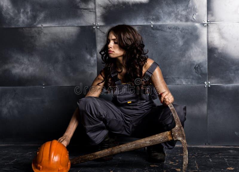 有镐的性感的女性矿工工作者,在他的赤裸身体的工作服 色情产业概念 图库摄影