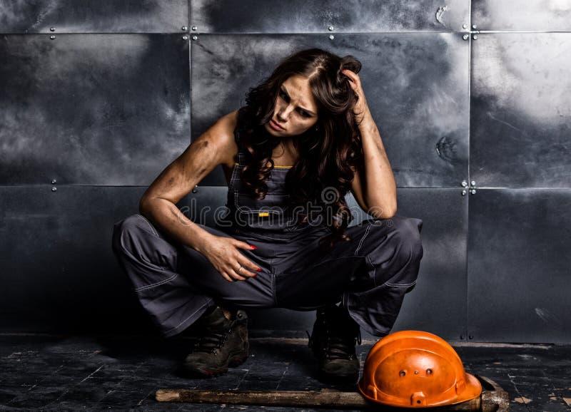 有镐的性感的女性矿工工作者,在他的赤裸身体的工作服 色情产业概念 免版税库存图片