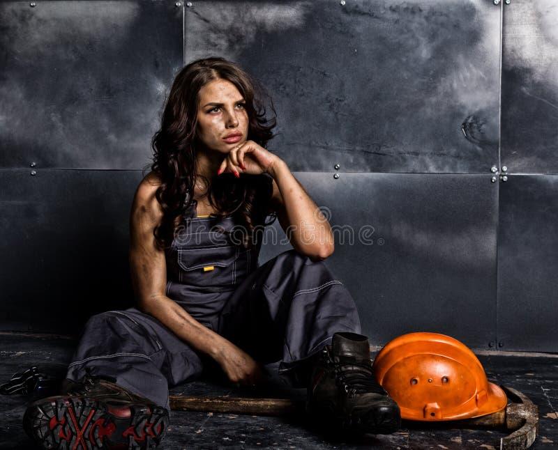 有镐的性感的女性矿工工作者,在他的赤裸身体的工作服 色情产业概念 库存照片