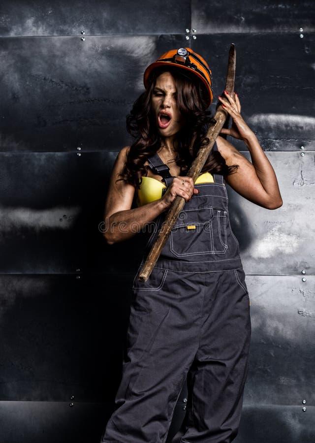 有镐的性感的女性矿工工作者,在他的赤裸身体的工作服 免版税库存图片