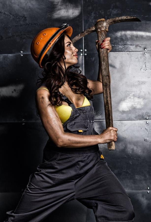 有镐的性感的女性矿工工作者,在他的赤裸身体的工作服 库存图片
