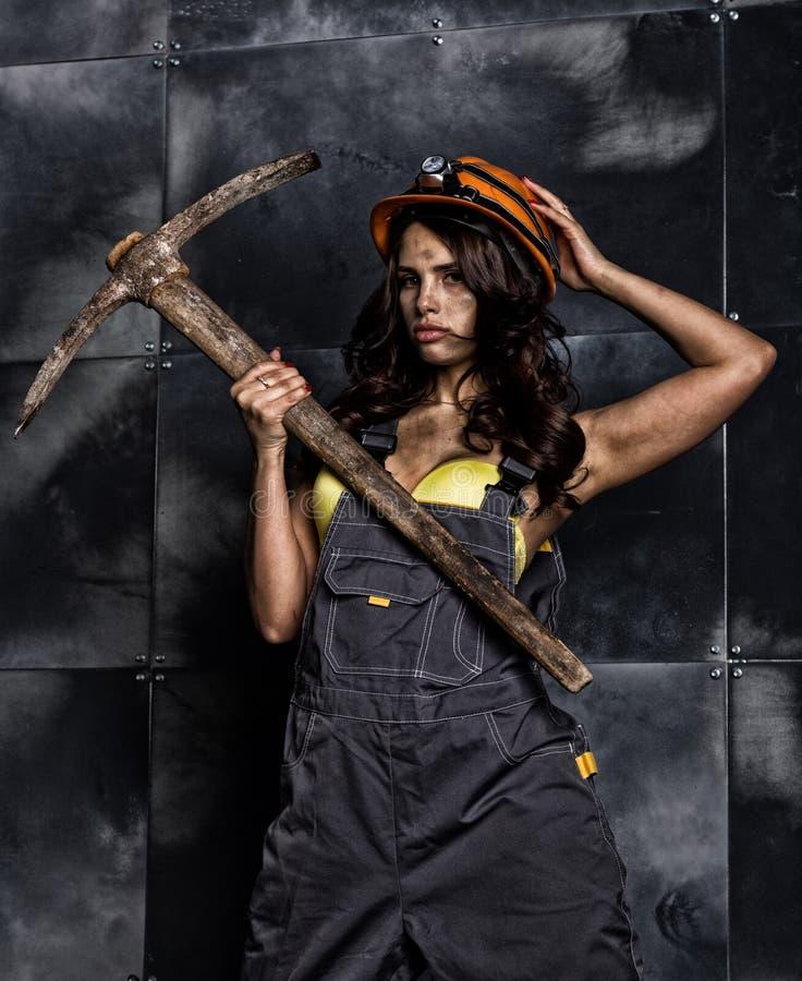 有镐的性感的女性矿工工作者,在他的赤裸身体的工作服 免版税库存照片