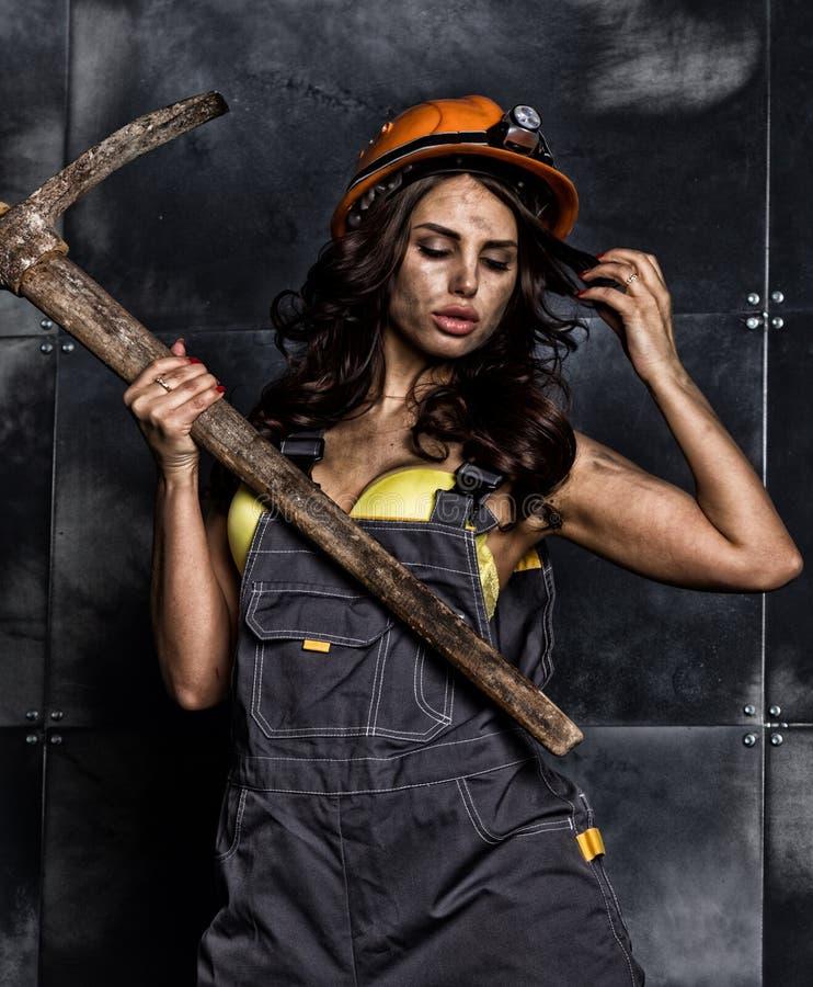 有镐的性感的女性矿工工作者,在他的赤裸身体的工作服 图库摄影