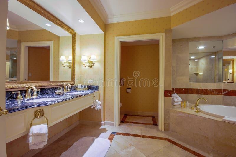 有镜子两水槽极可意浴缸浴缸的现代卫生间为h轻拍 免版税库存图片