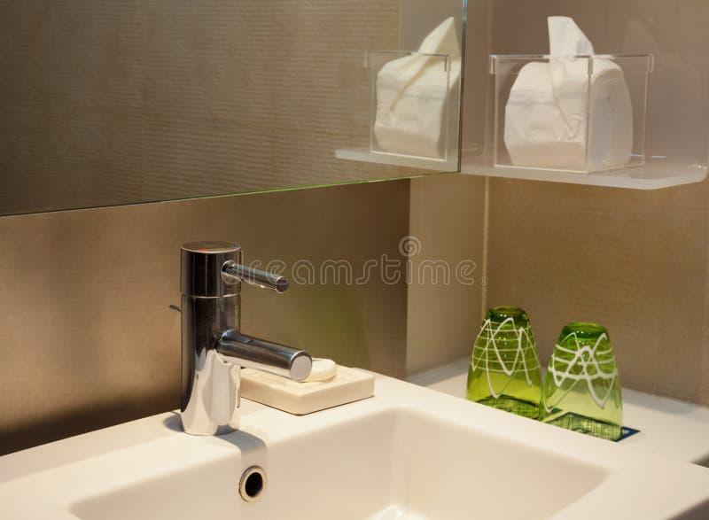 有镜子和布朗瓦片的现代润肤水龙头 库存照片