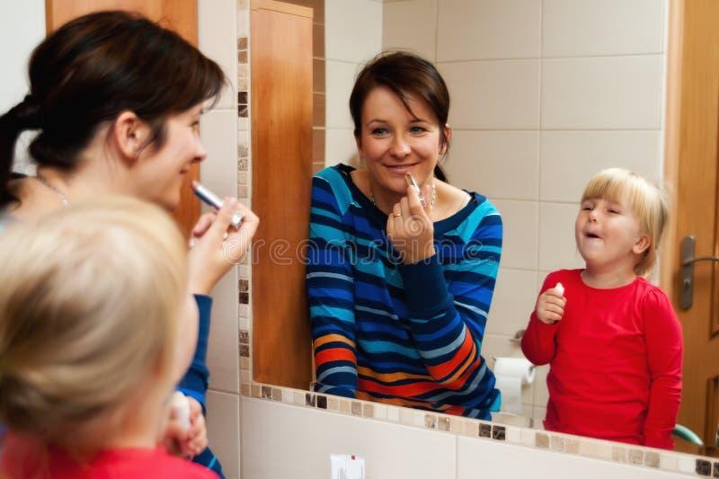 有镜子的母亲和女儿 图库摄影