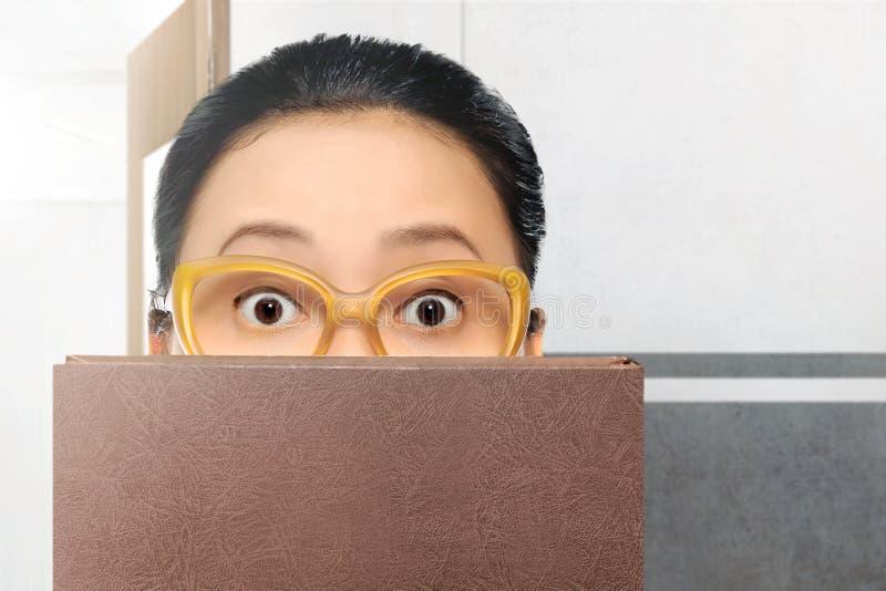 有镜片和书的美丽的亚裔学生妇女 免版税库存图片