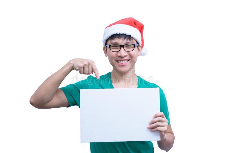 有镜片和绿色衬衣的亚裔圣诞老人项目人在白色背景有拿着一副白色空白的广告横幅被隔绝 免版税库存图片