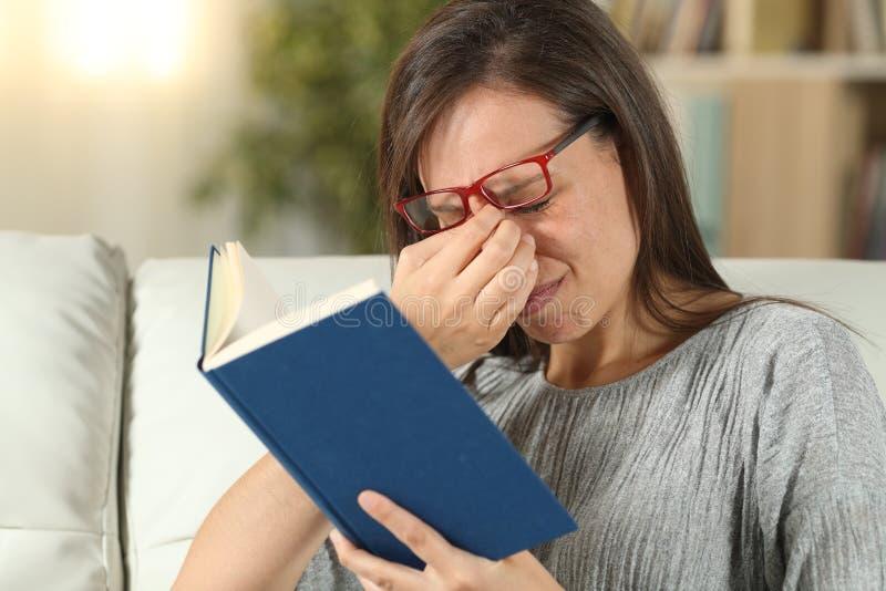 有镜片的妇女遭受累眼读书的 免版税库存照片