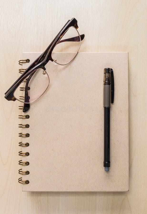 有镜片的布朗笔记本和在木背景的黑笔 免版税图库摄影