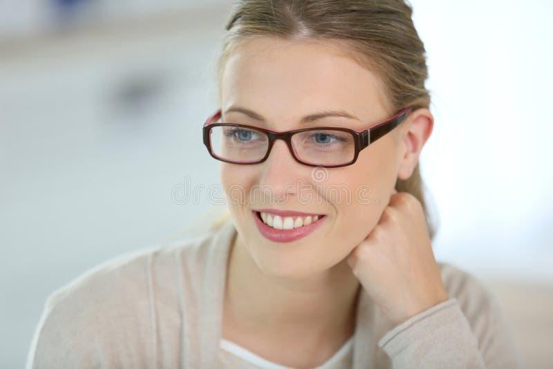 有镜片的微笑的美丽的妇女 库存照片