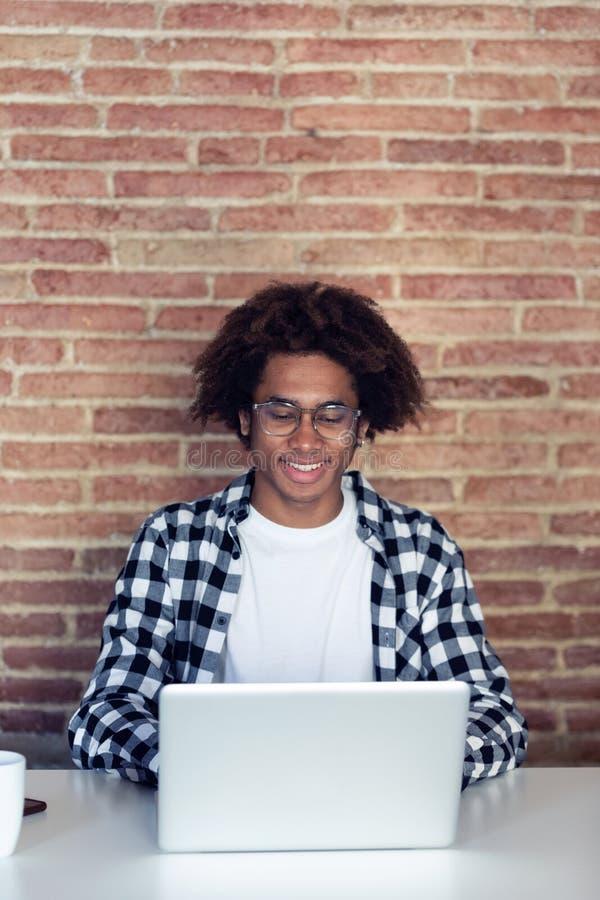 有镜片的英俊的年轻美国黑人的人使用他的膝上型计算机在家 库存照片