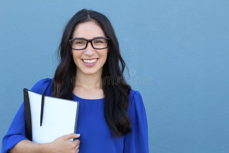 有镜片的年轻女商人在蓝色背景 免版税库存照片