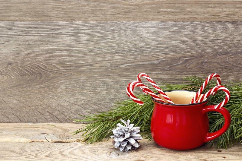 有镶边圣诞节棒棒糖的红色杯子反对木backg 免版税库存照片